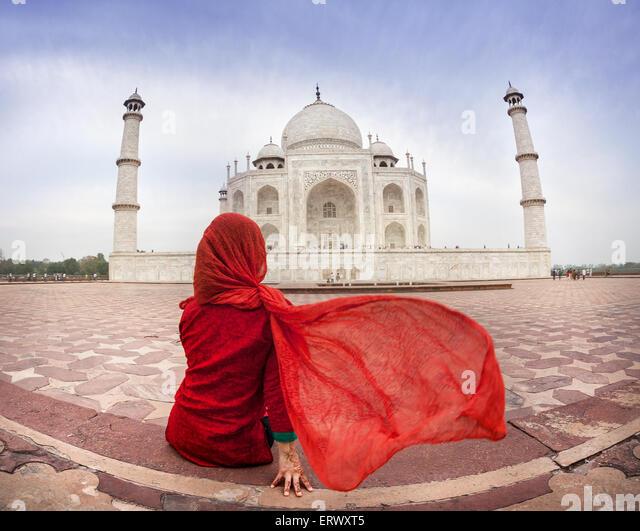 Woman in red costume with flattering scarf sitting near Taj Mahal in Agra, Uttar Pradesh, India - Stock Image