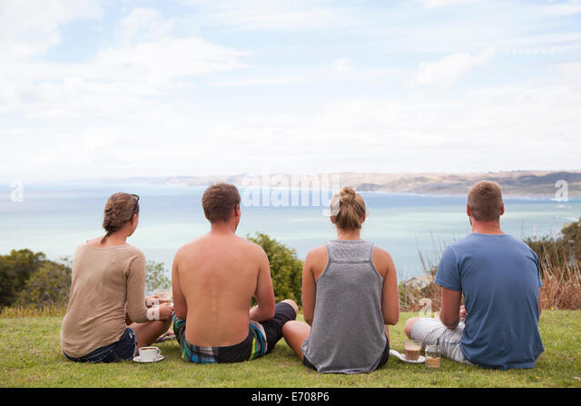 Rear view of four friends sitting looking away to sea - Stock-Bilder