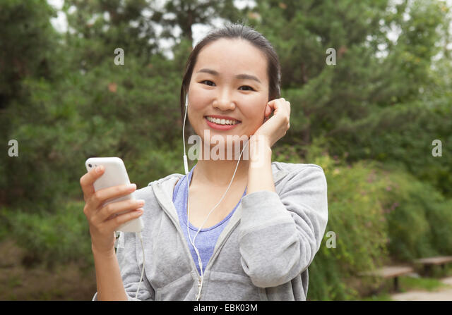 Portrait of young female runner selecting music from smartphone in park - Stock Image