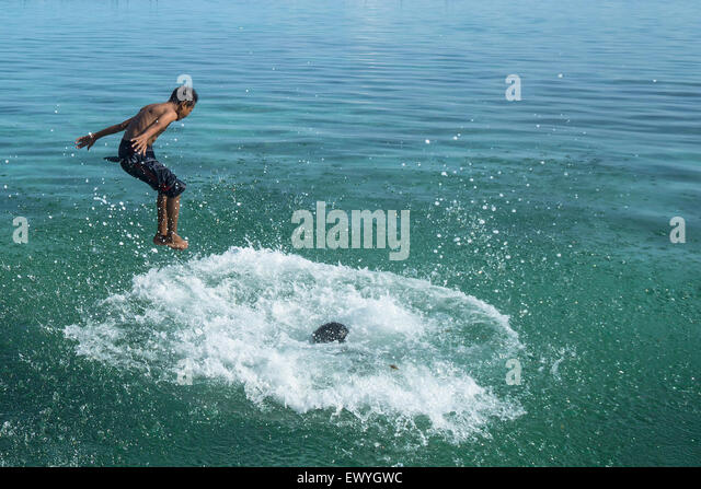 Two boys jumping into the sea, Salakan Island, Semporna, Sabah, Malaysia - Stock Image