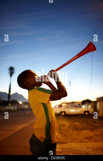Boy playing vuvuzela horn at Guguletu Township in the evening, Cape Flats, Cape Town, South Africa, Africa - Stock-Bilder