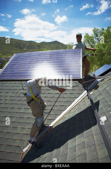 Construction workers installing solar panels on roof - Stock Image