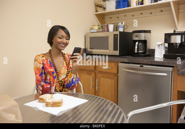 Mixed race businesswoman eating lunch in break room - Stock Image