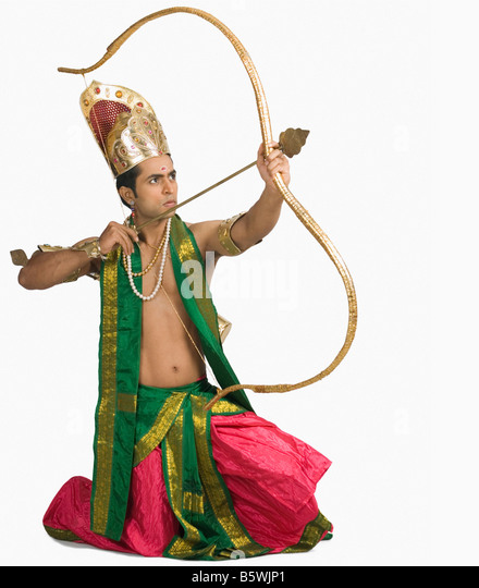 Young man in a character of Arjuna and holding a bow and arrow - Stock Image