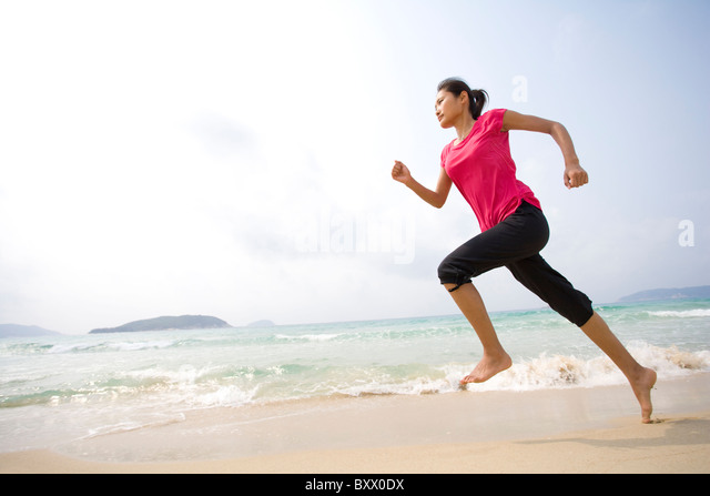 Young woman running on the beach - Stock-Bilder