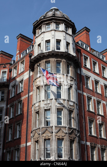 Tall historical building in London with a Union Jack flag hanging from the wall - Stock Image