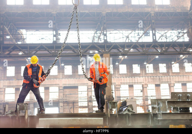 Steel workers with crane hooks in factory - Stock Image