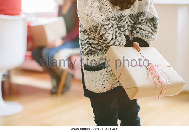 Child hiding surprise gift at family Christmas party - Stock Image