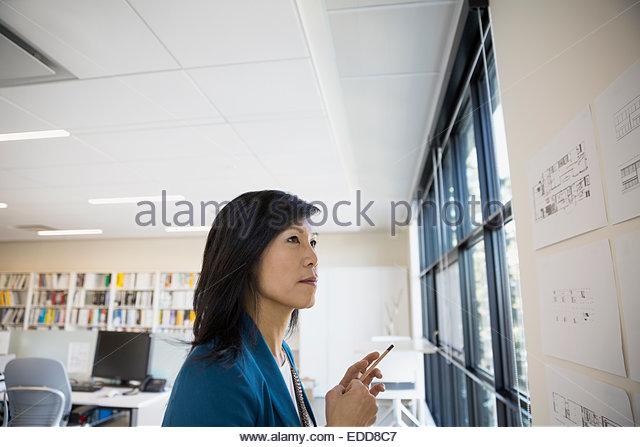 Architect examining plans on wall - Stock Image