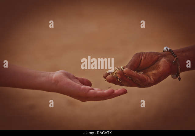 Hand giving rice to other hand - Stock-Bilder