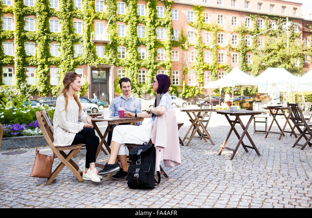 Friends discussing at sidewalk cafe in town square - Stock Image