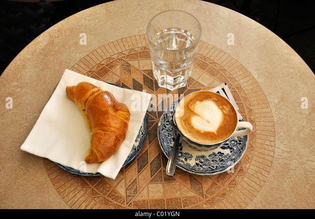 A European classic continental breakfast: a croissant and a cappuccino. Stock Photo