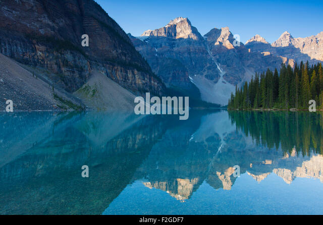 Mountains reflected in glacial water of Moraine Lake in the Valley of the Ten Peaks, Banff National Park, Alberta, - Stock Image