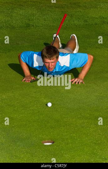 A golfer lining up a put on the green. - Stock-Bilder