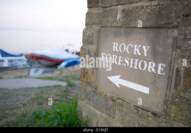 Sign to a Rocky Foreshore with boats in background - Stock Image