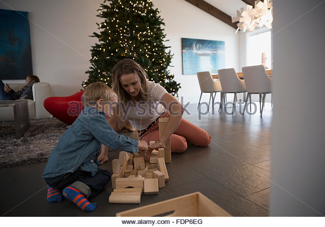 Mother and son playing wood blocks Christmas tree - Stock Image