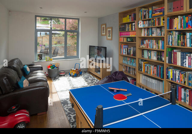 Playroom showing table tennis table, bookcases and toys in a moden family home. - Stock Image