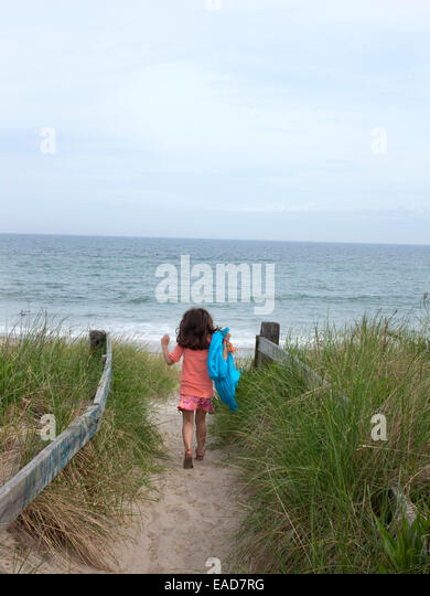 young girl enthusiastically entering beach - Stock Image