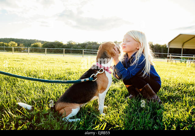 Caucasian girl kissing puppy on farm - Stock Image