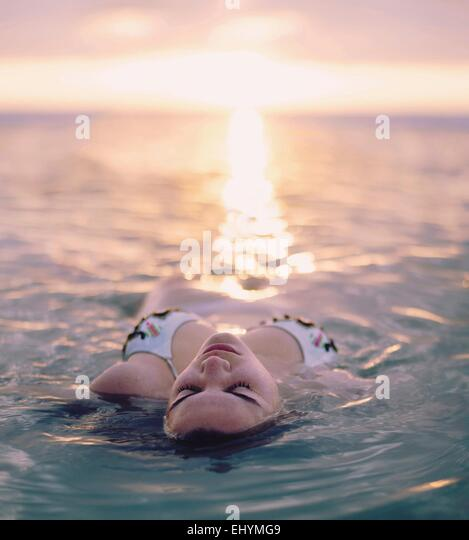 Young woman floating in the sea, Sanibel Island, Florida, USA - Stock Image