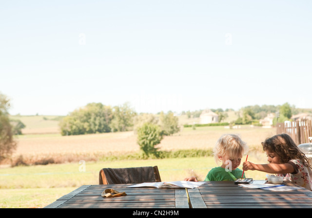 Brother and sister painting outside - Stock-Bilder