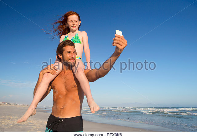 Father, with daughter sitting on shoulders, taking selfie on sunny beach - Stock Image
