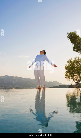 Man stands in open space sky and reflective pool arms out. - Stock Image