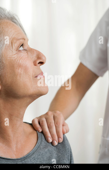 Senior woman being comforted by another woman, cropped - Stock Image