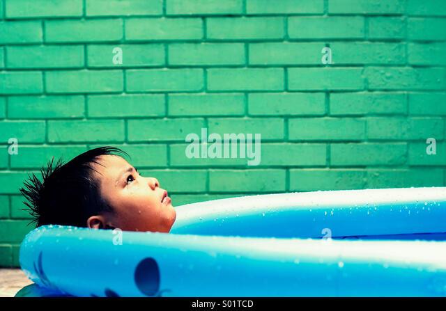 Kid in a kiddie pool - Stock Image