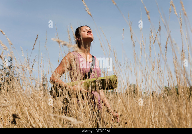 A young woman enjoys the sun on her face as she stands in a field of golden grasses holding a yoga mat. - Stock Image