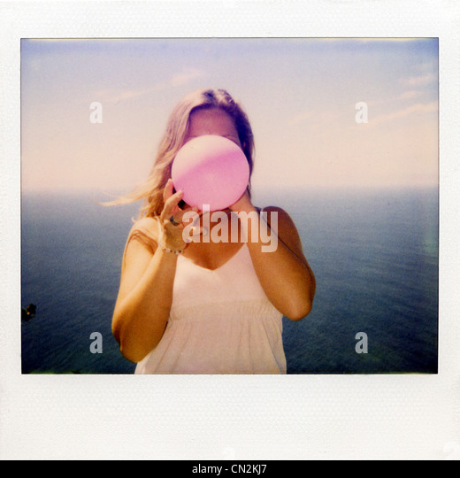 Instant film photograph of woman blowing up balloon - Stock Image