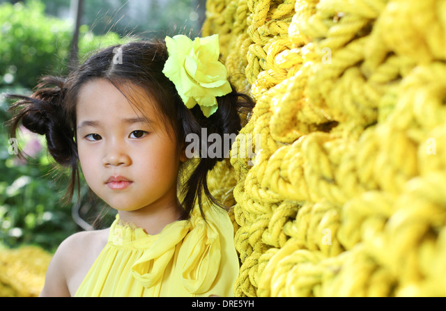 Young asian girl surrounded by yellow - Stock Image