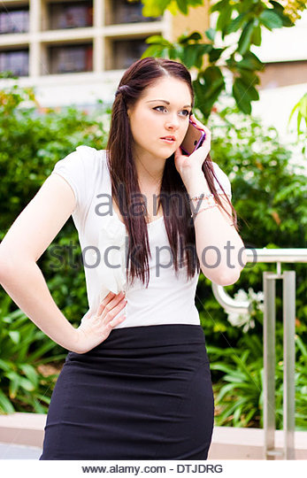 Irritated And Upset Business Woman Showing Displeased Body Language When Talking On A Mobile Phone Outdoors In A - Stock Image