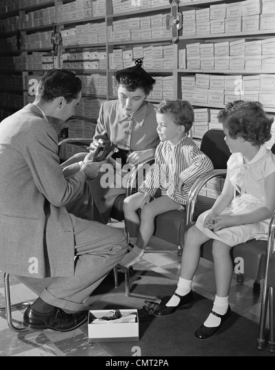 1950s FAMILY MOTHER TWO CHILDREN IN SHOE STORE TRYING NEW SHOES HELPED BY SALESMAN - Stock Image