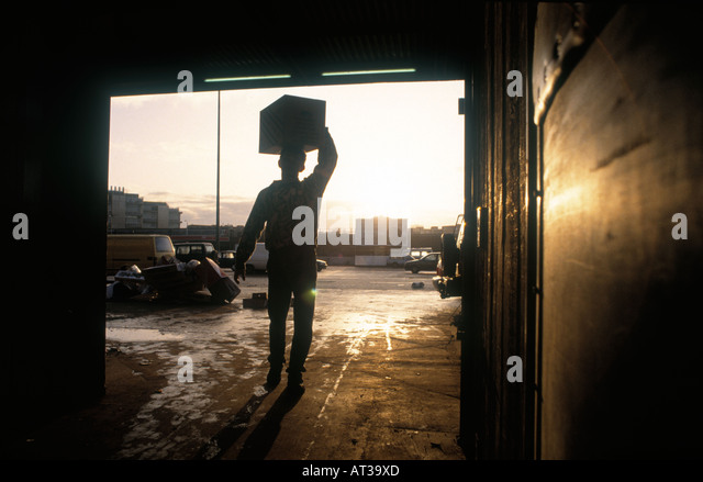 Man carrying box of vegetables at the New Covent Garden Market that is the largest wholesale market in UK - Stock Image