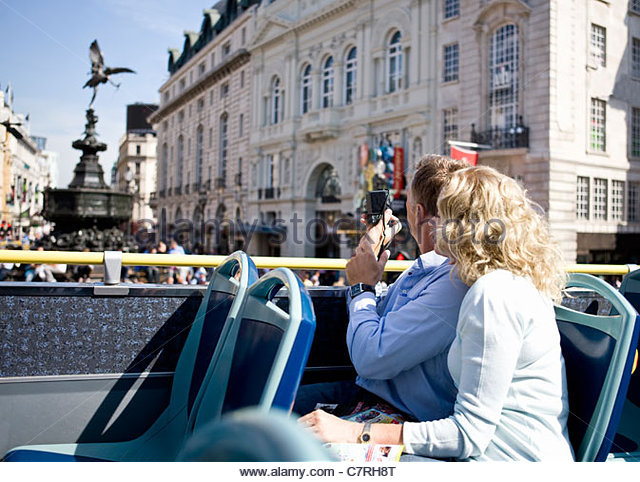 A middle-aged couple sitting on a sightseeing bus, taking photographs - Stock Image
