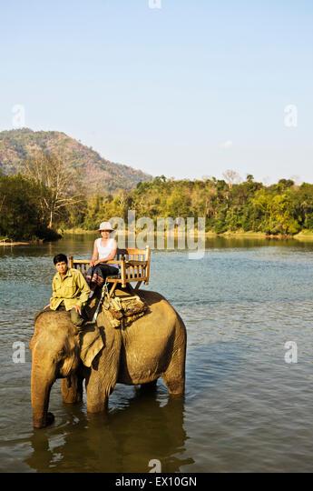 A Lao woman and mahout ride an elephant on the Khan River. Luang Prabang, Laos. - Stock-Bilder