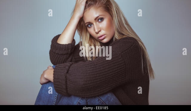 Portrait of beautiful blond female in sweater looking at camera. Pretty young woman in studio. - Stock Image
