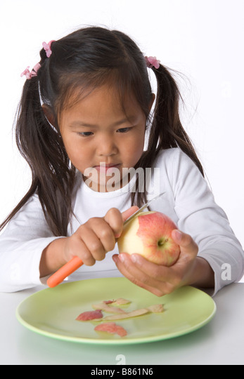 Little girl is peels an apple with a knife - Stock Image