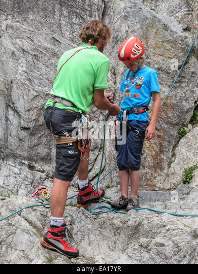 A young boy with his climbing instructor getting ready to climb a rock face.  Wearing helmet, harness and climbing - Stock Image