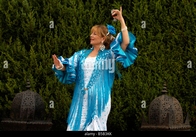 Spanish woman dancing with a glass of fino sherry, Fuengirola Feria, Costa del Sol, Andalucia, Spain Europe, - Stock Image