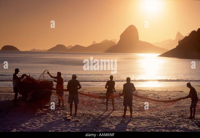Fishermen in Niterói twin city of Rio de Janeiro in background Brazil Sugar Loaf Mountain and Rio de Janeiro - Stock-Bilder
