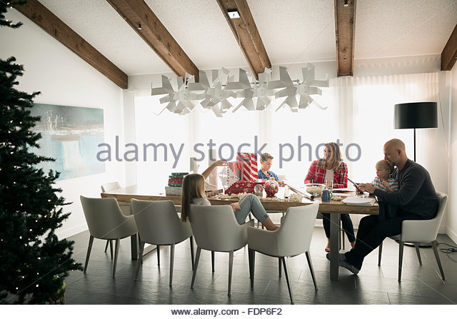 Family eating at dining table near Christmas tree - Stock Image
