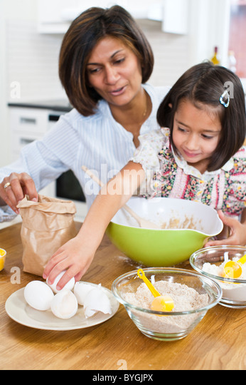 Mother baking with daughter in kitchen - Stock-Bilder