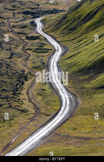 Dirt road & moss covered mountains, Landmannalaugar, Southern Highlands, Iceland - Stock Image