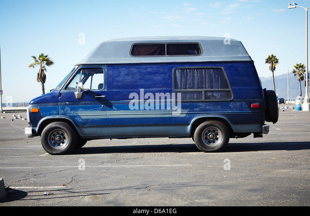 Minivan sitting in parking lot - Stock Image
