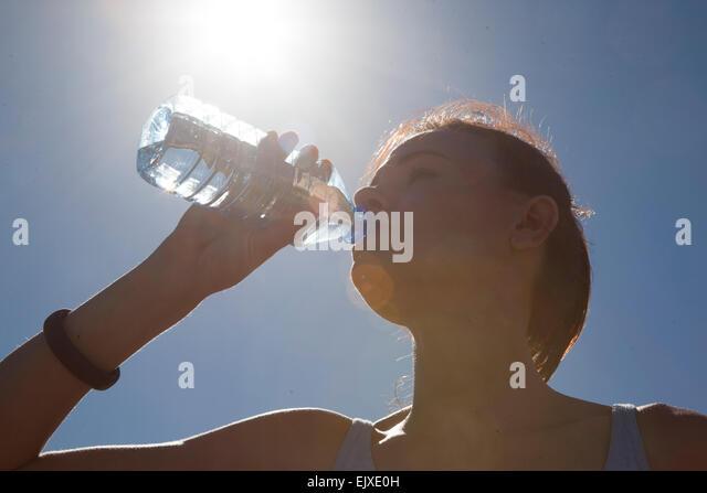 Woman Drinking Water from Bottle against Blue Sky - Stock-Bilder