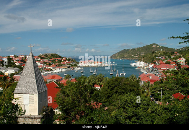 ST BARTS French West Indies Gustavia Harbor Overview buildings orange roofs, trees mountains - Stock Image