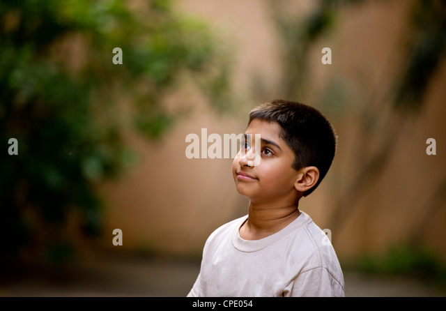 an young handsome Indian kid day dreaming - Stock Image