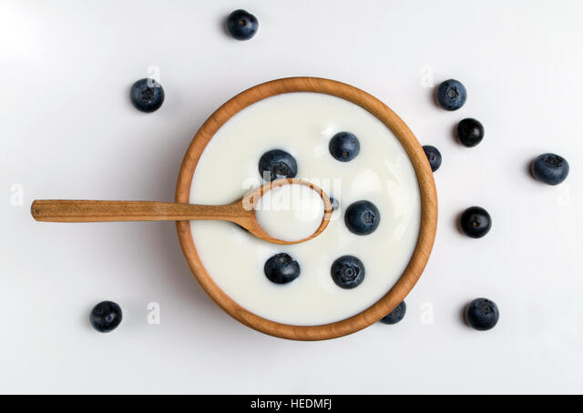 White yogurt in natural wooden bowl with blueberries. Top view. - Stock Image